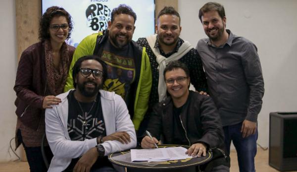 Da esquerda para a direita. De pé: Renata Cenízio (gerente artístico da gravadora), Alex Passos (idealizador do grupo Preto no Branco), Amandio Lessa (também responsável pela banda) e Miguel Cariello (diretor de A&R da gravadora). Sentados: Clóvis Pinho (vocalista do Preto no Branco) e Paulo Lima (presidente da Universal Music Brasil)